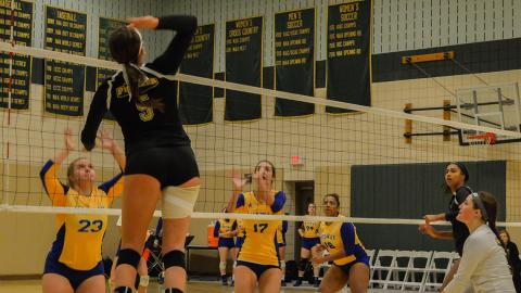Meg Reineke (5) goes up for a kill versus Midway. Photo by Megan Bixler.